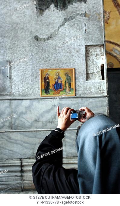 Nun taking a photo inside The Haghia Sofia Mosque, Istanbul, Turkey
