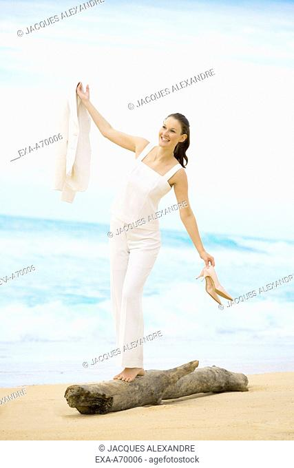 Woman balancing on a trunk at the beach