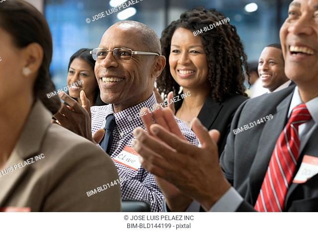 Business people clapping in presentation in office