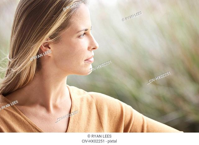 Close up pensive blonde woman looking away