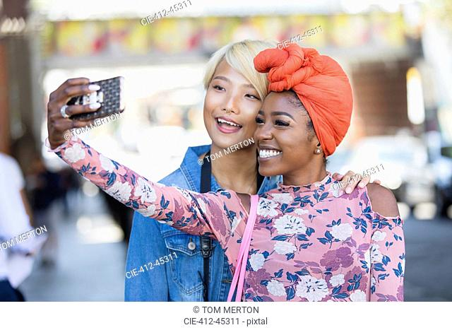 Happy young women taking selfie with camera phone