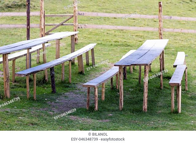 Picnic place for rest on green grass. Lit by bright summer sun old weathered wooden tables and benches on primitive fence made from beams background