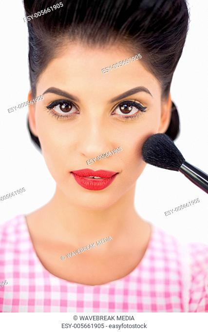 Gorgeous black hair model applying powder on her cheek