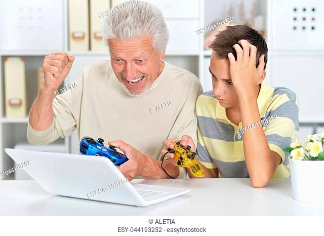 Portrait of boy and grandfather playing computer game with a laptop at home