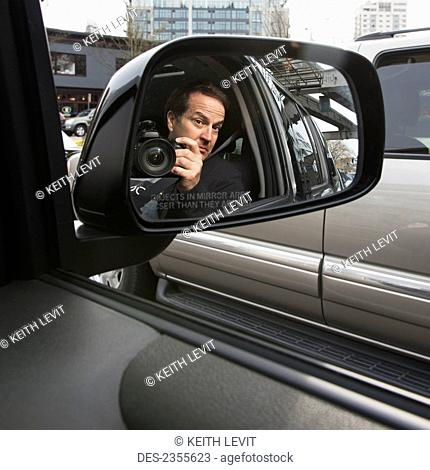 A Man With His Camera Reflected In A Car's Side View Mirror; Seattle, Washington, United States Of America