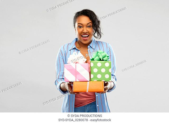 happy african american woman with birthday gifts