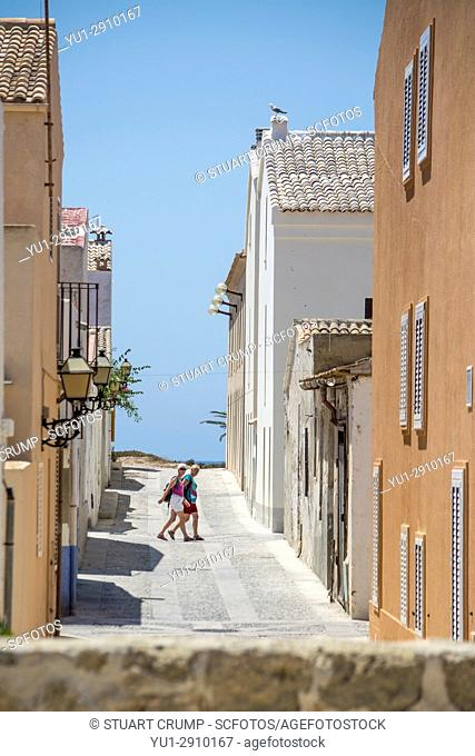 Couple of tourists walking along the narrow streets on the island of Tabarca Spain