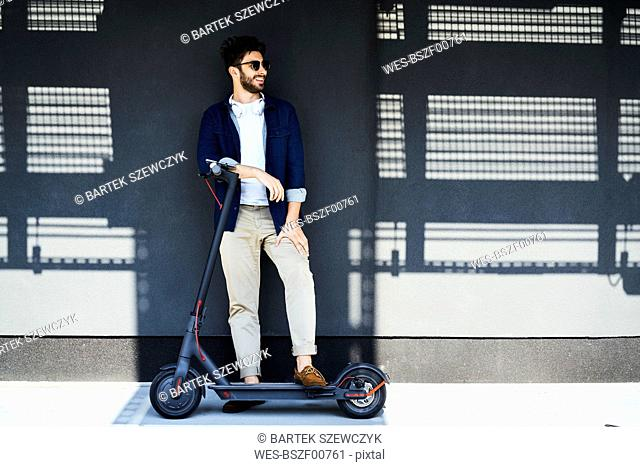 Smiling man with electric scooter outdoors