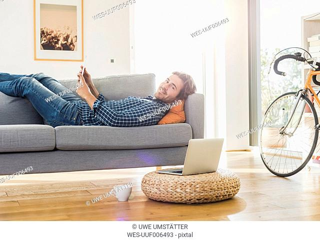 Young man with digital tablet lying on the couch at home