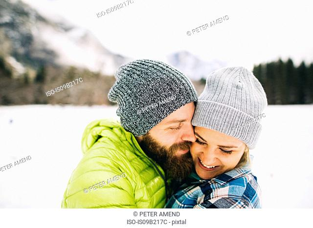 Couple on snow-covered landscape wearing knit hats hugging
