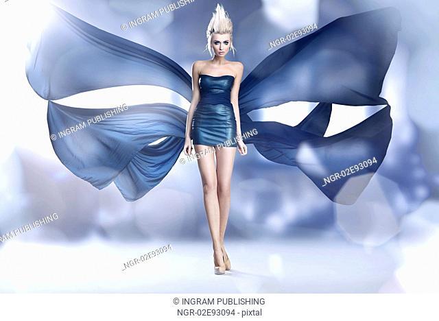 Beautiful woman as an amazing butterfly in blue dress
