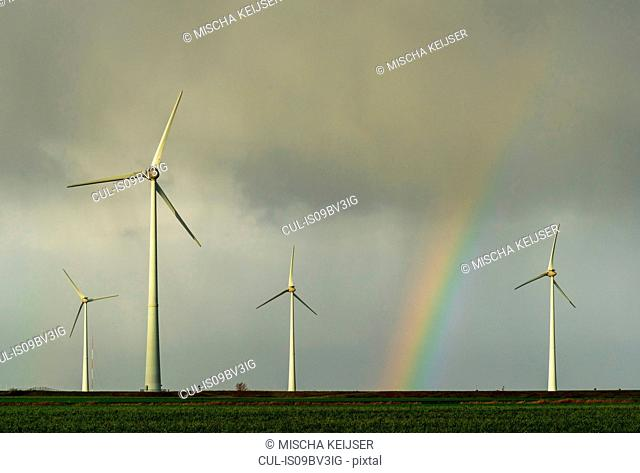 Field landscape with rainbow between turbines on wind farm in north Netherlands, near waddensea dyke