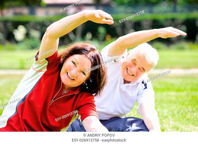 Happy Senior Couple Exercising In Park At Morning