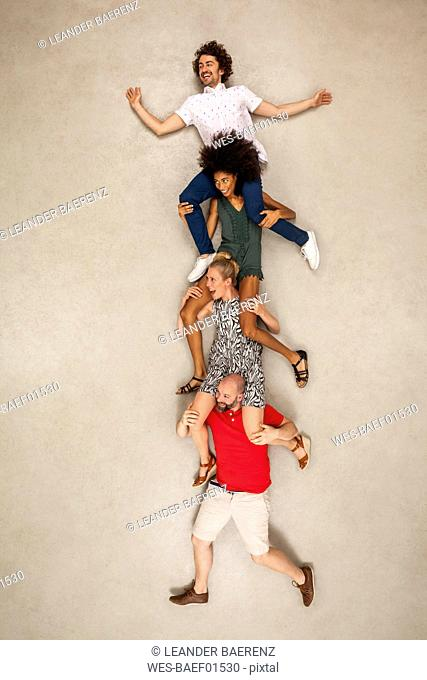 Group of people sitting on each other's shoulders