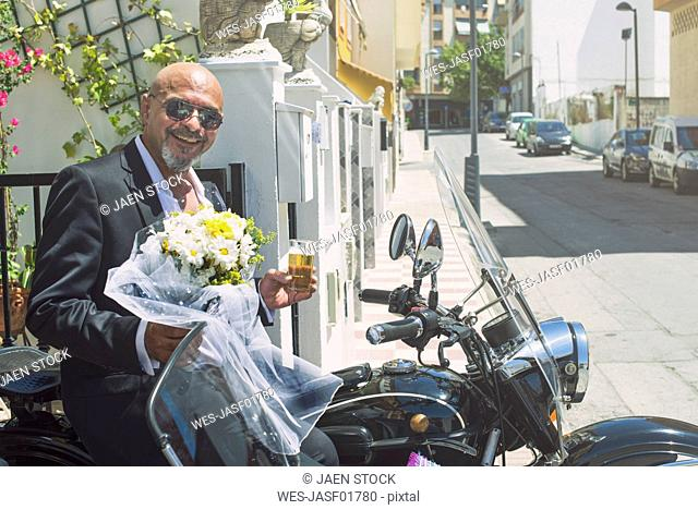 Portrait of smiling biker on his sidecar motorcycle with glass of beer and bunch of flowers