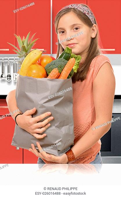 a young teen, holding grocery shopping bag with vegetables Standing in the kitchen
