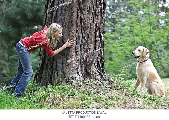 Girl playing hide and seek with dog