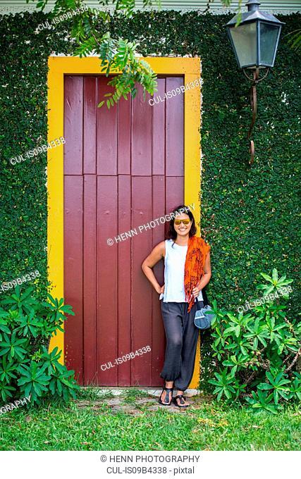Woman leaning against yellow door frame, Paraty, Costa Verde, Rio de Janeiro, Brazil