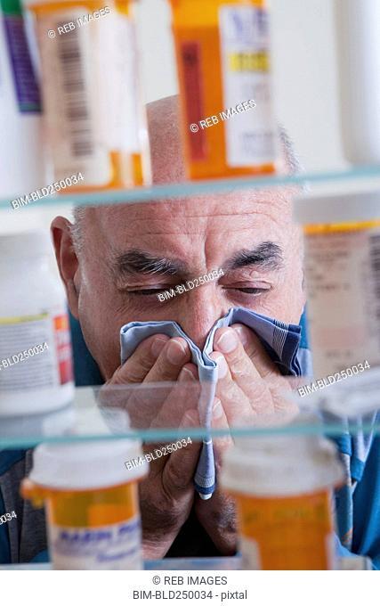 Hispanic man wiping nose near medicine cabinet