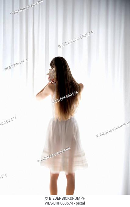 Young woman standing with a shell in front of a white curtain, back view