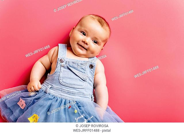 Portrait of smiling baby girl lying on pink background