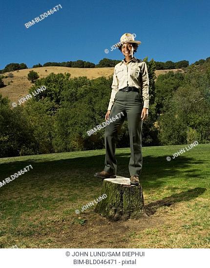 African American Park Ranger standing on tree stump