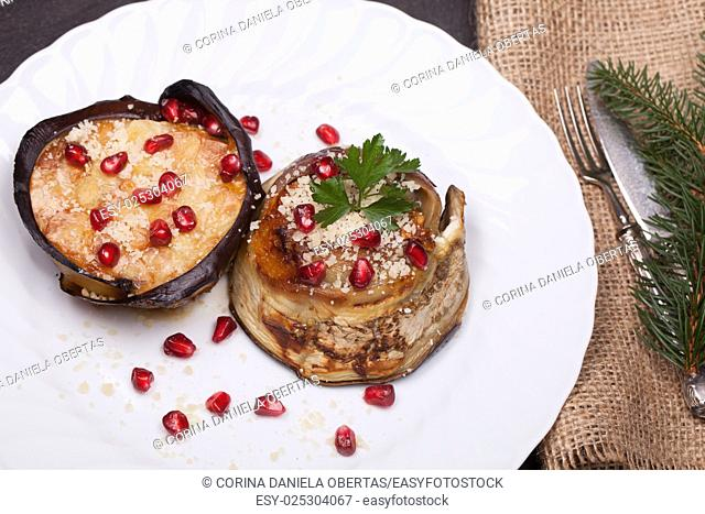 Fresh baked eggplant zuccotto, decorated with pomegranate seeds on Christmas table. Eggplant zuccotto is a traditional dish of the Italian cuisine