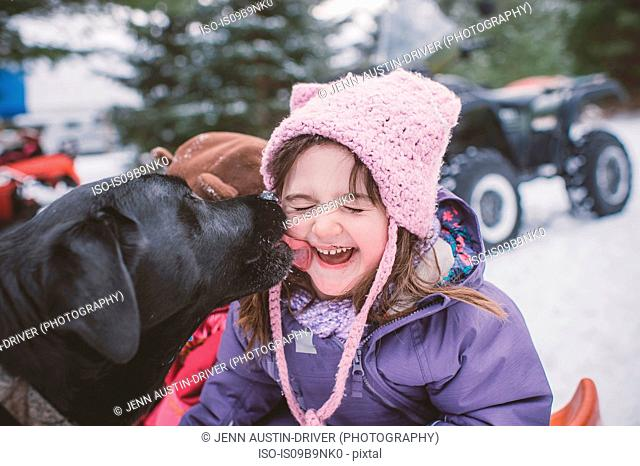 Young girl with dog in snowy landscape, dog licking girl's face