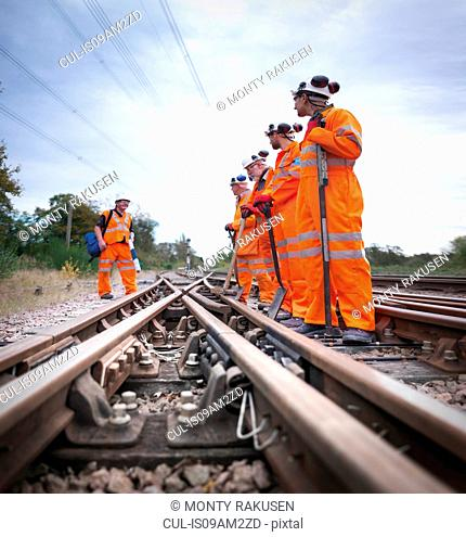 Safety officer with group of railway maintenance workers standing on track