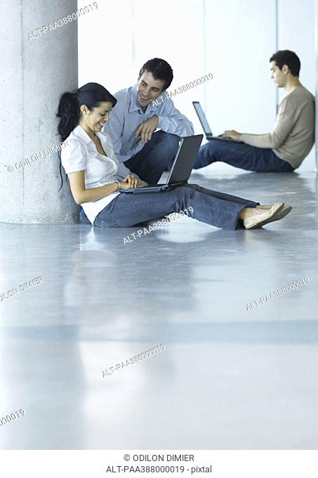 Man and woman on floor, using laptop and talking, second man in background