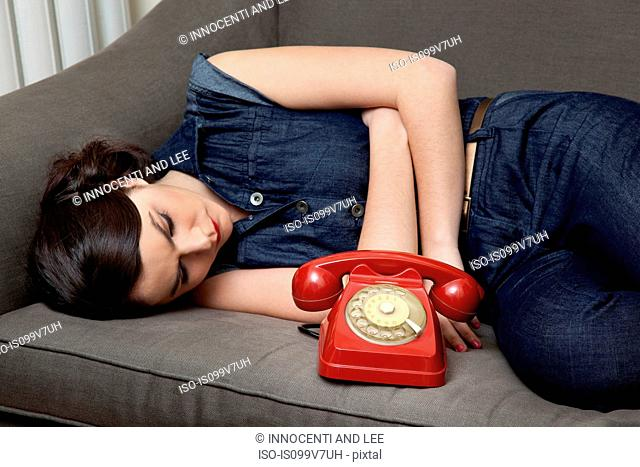 Woman lying on sofa with telephone