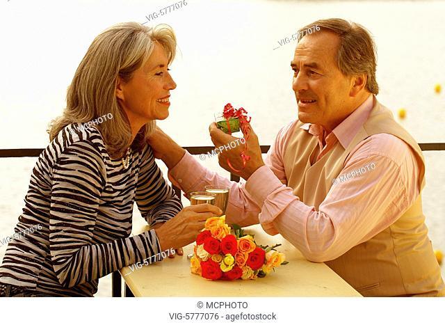 Ein verliebtes aelteres Paar hat einen Grund zum feiern und stoesst mit Sekt an, Hamburg 2006 - Hamburg, Germany, 11/09/2006