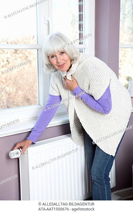 Freezing woman turning the heating up