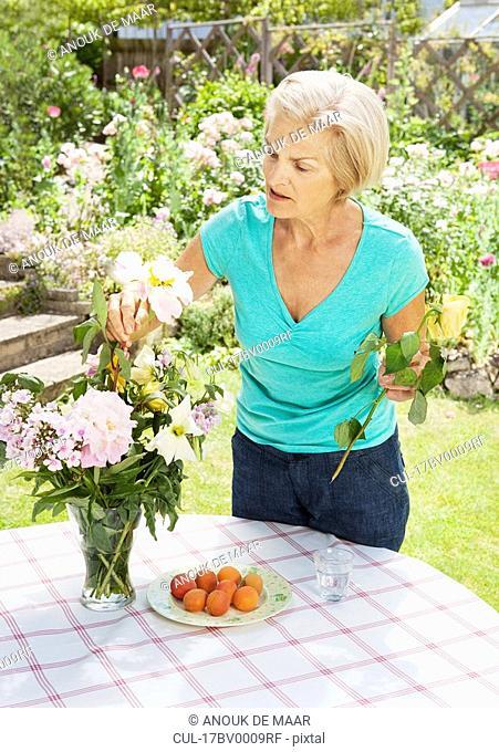 mature woman arranging flowers in vase