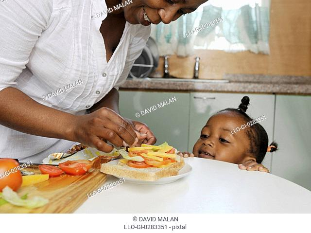 Mother preparing a sandwich for her daughter. Cape Town, South Africa