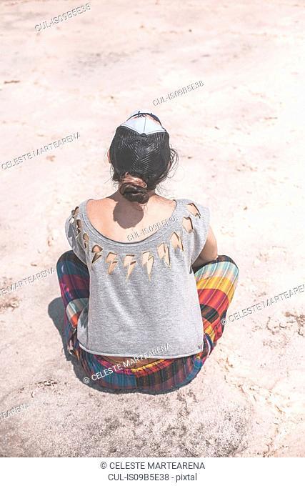 Woman sitting on salt flats, rear view, Jujuy, Salinas Grandes, Argentina