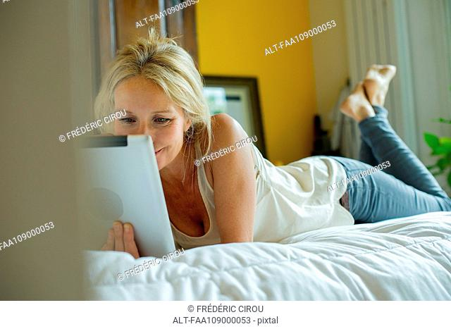 Mature woman lying on bed watching digital tablet