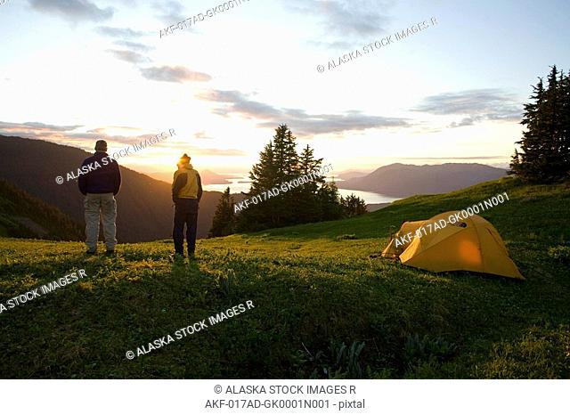 Two climbers standing outside their tent in the evening light at alpine camp on Eagle Peak Admiralty Island Southeast Alaska Summer