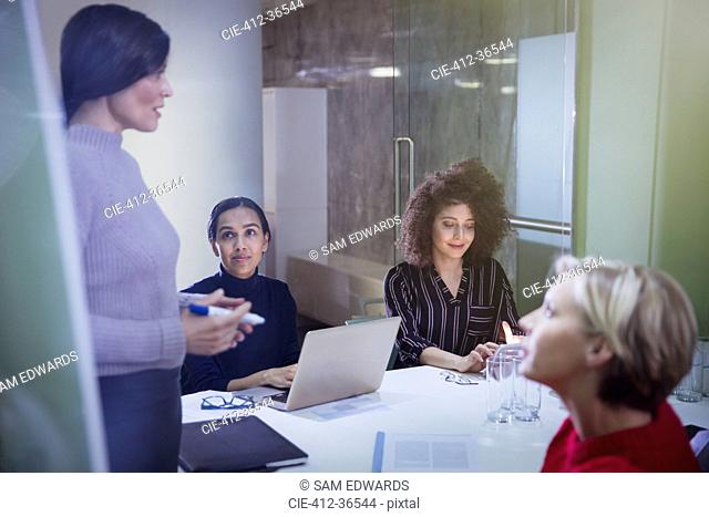 Businesswomen planning, talking in conference room meeting