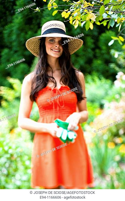 25 year old brunette woman in a garden settng wearing a dress and a straw hat, looking at the camera