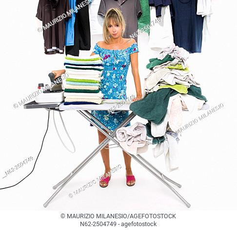 Woman with angry expression ironing on board many clothing