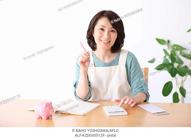 Senior Japanese woman doing accounting in the living room