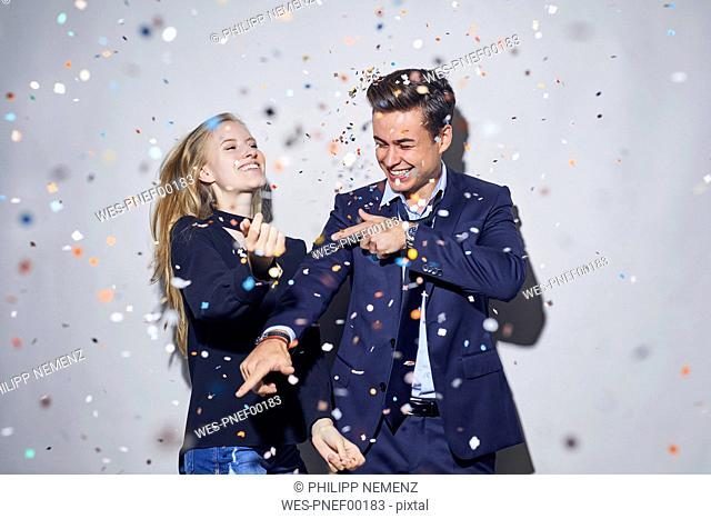 Two young businesspeople dancing under shower of confetti