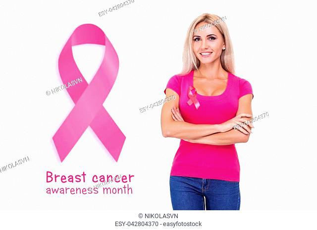 healthcare and medicine concept - smiling beautiful blonde woman in pink t-shirt with pink breast cancer awareness ribbon on the white background