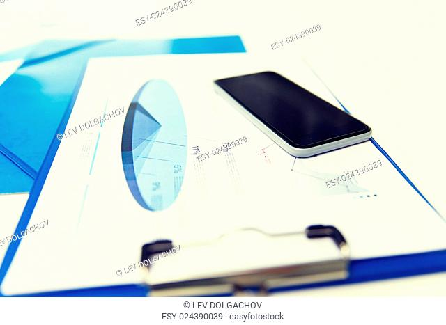 business, technology and statistics concept - close up of smartphone and clipboard with charts on office table