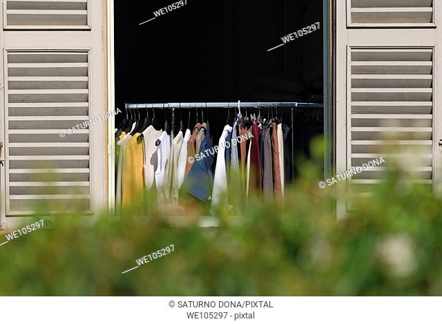 Hanging clothes, open window behind hedge
