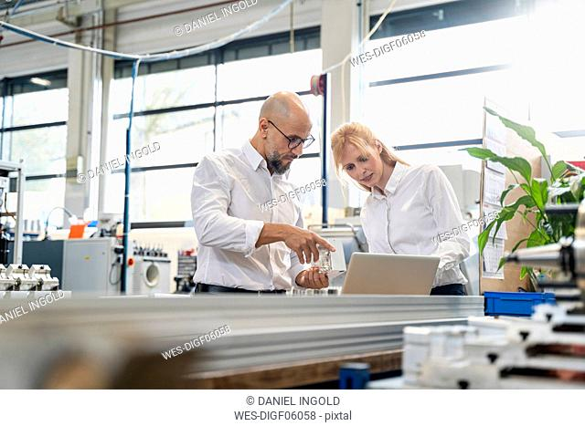 Businessman and businesswoman with laptop examining workpiece in factory