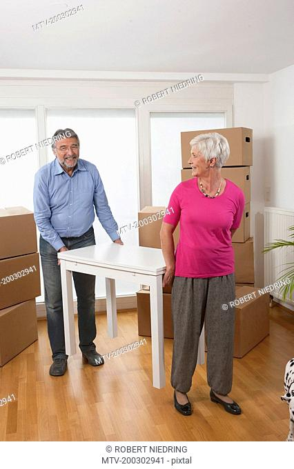 Senior couple moving a table in new apartment, Bavaria, Germany