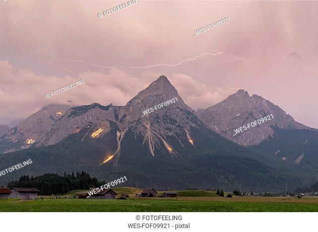 Austria, Lermoos, Ehrwalder Becken, Ehrwalder Sonnenspitze with midsummer fire, Gruenstein, Ehrwald, Mieminger Kette with thunderstorm and lightning