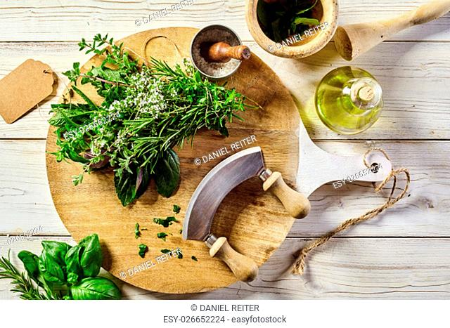 Mezzaluna knife with assorted fresh herbs and salt on a wooden chopping board with a pestle and mortar, blank tag and olive oil alongside, overhead view